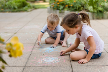 Children drawing with chalk outdoors