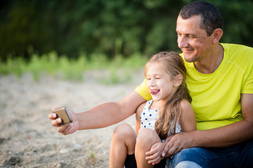 Smiling father taking selfie with young daughter outdoors