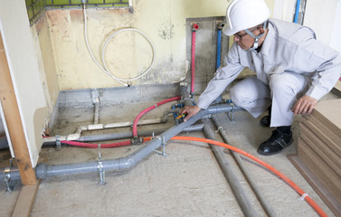 マンション・スクケルトンリフォーム・給排水工事・傾きをチェックする作業員