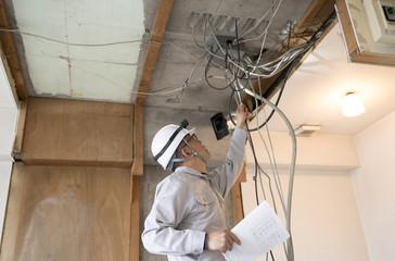 マンション・スクケルトンリフォーム・電気工事・図面を持ちながらチェックする作業員