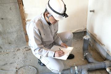 マンション・スクケルトンリフォーム・給排水工事・排水管をチェックする作業員