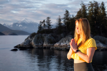 Young woman practicing yoga on a rocky island during a vibrant sunset. Taken in Whytecliff Park, Horseshoe Bay, West Vancouver, British Columbia, Canada.