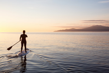 Adventurous girl on a paddle board is paddeling during a bright and vibrant sunset. Taken near Spanish Banks, Vancouver, British Columbia, Canada.