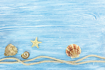 marine rope, seashells and starfish on blue shabby background. summer traveling concept
