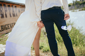Beautiful wedding couple, bride,groom kissing and posing on the bridge near lake