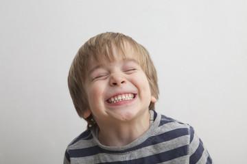 Niño (5 años) con los ojos cerrados y boca abierta mostrando los dientes. Expresión de júbilo,