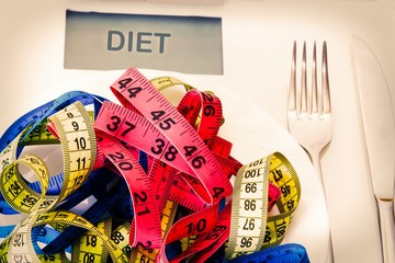 scales and metric tapes with steel cutlery. diet and slimming concept