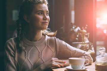 Caucasian woman dreaming about something while sitting with cup of coffee in modern cafe bar, young charming female freelancer thinking about new ideas during work. Toned. Sun glare
