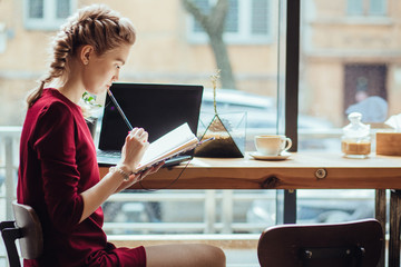 Beautiful Caucasian woman blogger writting plans in notebook while sitting with laptop in modern loft cafe bar, female student freelancer thinking about new ideas during work on laptop computer.