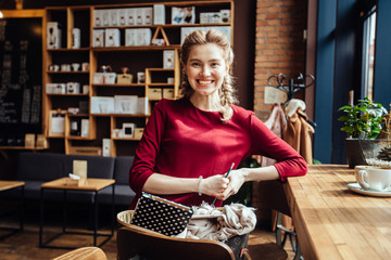 Portrait of gorgeous young pleasent business woman nice to meet you in modern loft cafe interior.