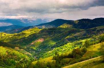 springtime in mountainous countryside. lovely rural landscape with forested hills and agricultural fields on a cloudy day
