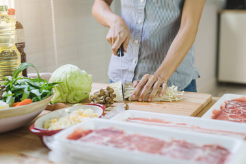 Young asian woman cutting vegetable in the kitchen