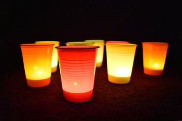 Glow plastic cups stock images. Colorful party cups. Colored cups on a dark background