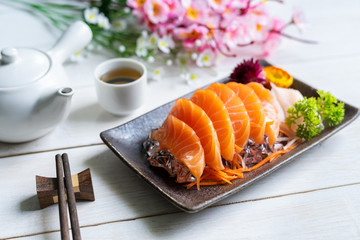 Salmon sashimi slice fresh serve on ice with tea, Japanese style