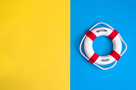 Lifebuoy on a yellow and blue background with blank space for text. Top view travel or vacation concept. Summer background. Flat lay photo, top view.