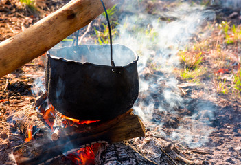 cauldron in steam and smoke on open fire