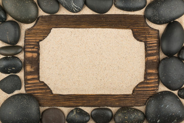Frame of dark wood in the sand and black stones around.