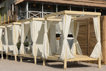 Beach bungalows are lined up in a row on the sand, the concept of leisure