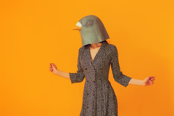 Woman portrait wearing pigeon mask and floral dress