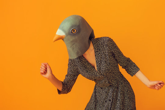 Woman portrait wearing pigeon mask and going to run
