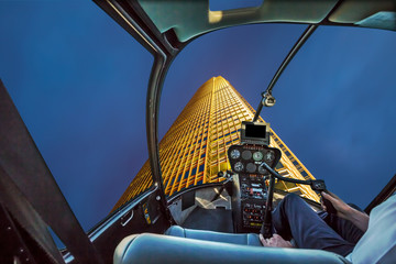 Helicopter cockpit flying on night skyscaper facade in hong kong.
