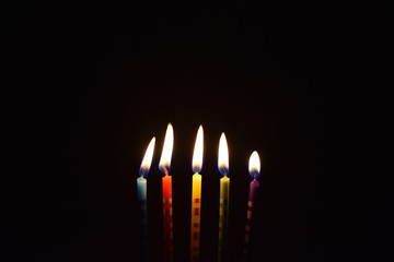 Colored candles on a dark background stock images. Burning cake candles. Birthday background images. Party candles on a black background
