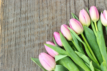 Top view of a bouquet of pink tulips on a wooden background