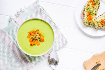 Top view Bowl of Green peas cream soup with baked carrot and microgreen sprouts on the served white wooden table. Healthy food, vegitarian diet concept. Selective focus, space for text.