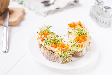 Healthy sandwiches for breakfast with humus, baked carrot and microgreen sprouts on the served white wooden table. Healthy food, vegitarian diet concept. Selective focus, space for text.