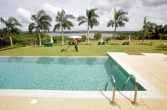 A worker mows the lawn at L'Autre Rive hotel in Dabou