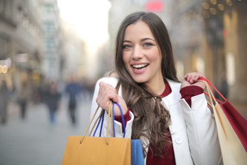 Beautiful young woman shopping in a big city and going crazy for that