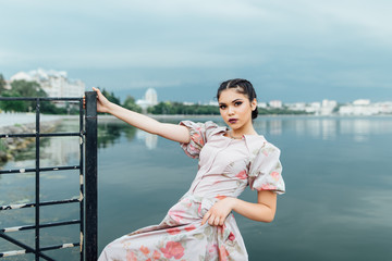 The girl on the bank of the lake. The girl is dressed in a beuti