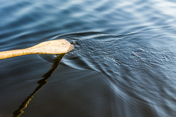 Closeup of oar paddle from row boat moving in water on green lake with ripples sport background
