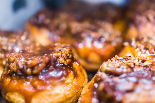 Macro closeup display of chocolate drizzled pecan nut sticky buns danish pastries caramelized in bakery for breakfast background