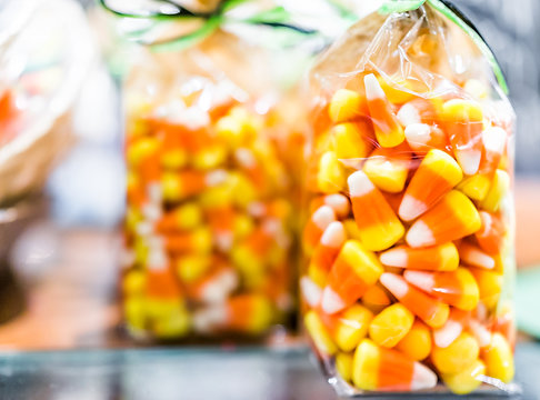 Closeup of colorful orange yellow candy corn on display packaged in plastic bag in candy store shop for Halloween holiday season trick or treat background