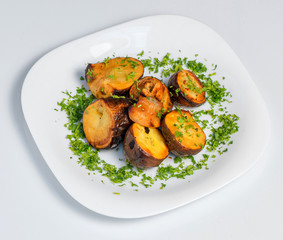 Roasted potato on black plate on white background
