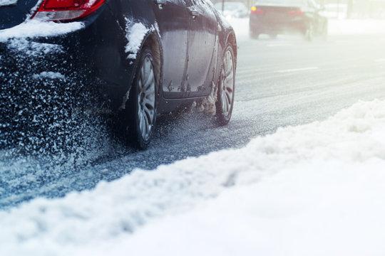 closeup of a car wheel going through snow