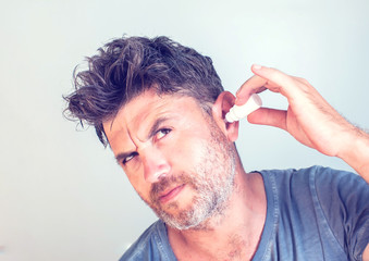 man using ear drops on gray background
