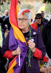 A woman carries a flag and carnations as Republicans commemorate the 87th anniversary of the declaration of the Second Spanish Republic at the General Cemetery in Valencia