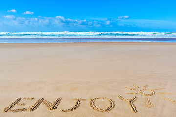 Enjoy inscription on wet beach sand under the sun drawing and sea waves on background
