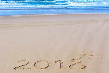 2018 inscription on wet beach sand and sea waves on background