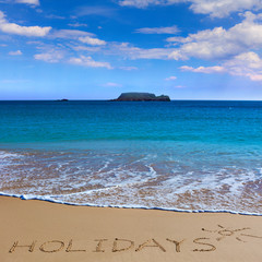 HOLIDAYS insctiption under the sun drawing on wet beach sand with the turquoisesea and the island on background