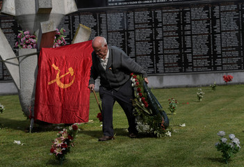Joaquin Alvarez, a relative of one of those executed and buried in mass graves during and after the 1936-1939 Spanish civil war, carries flowers in front of a memorial grave in Oviedo