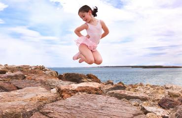 little girl jumping in a rocks beach