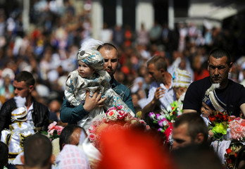 Bulgarian Muslim men and their sons ride horses as they attend a mass circumcision ceremony in the village of Ribnovo