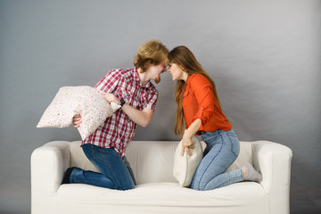 Angry couple having pillow fight