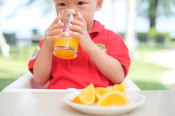 Cute little Asian 18 months / 1 year old toddler baby boy child sitting in high chair holding & drinking tasty orange juice in a glass at restaurant in beach resort, Selective focus and kid's hand