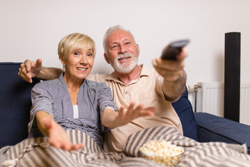 Senior couple lying on bed and watching TV together.