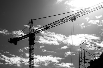Black and white photo of a silhouette of a construction crane and bright sun with clouds