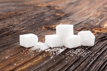 Sugar cubes on wooden table.